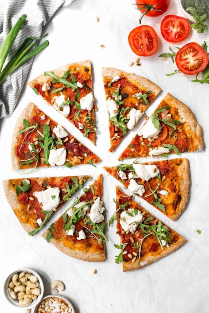 A hand reaching for slices of vegan pizza.