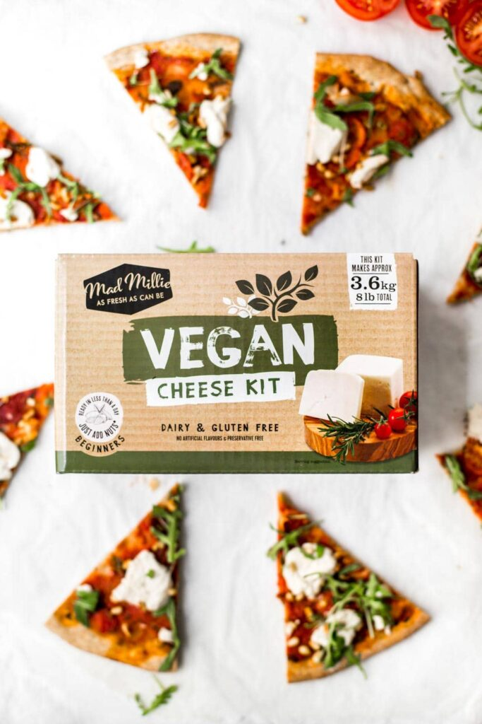 A box of Vegan Cheese Kit surrounded by slices of pizza.