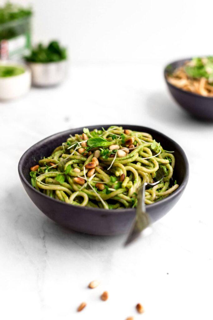 Creamy green pasta in a black bowl.