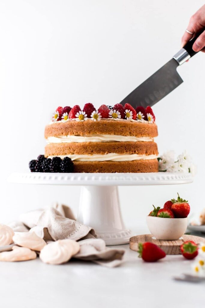 A knife cutting into a cake on a white stand.