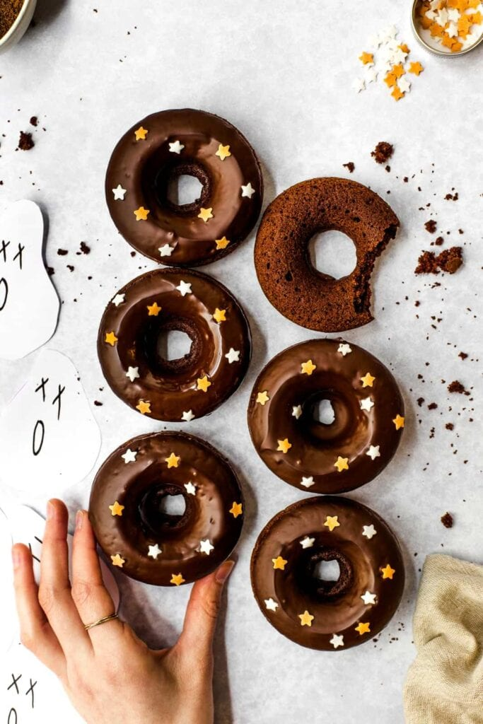 Six chocolate donuts and a hand coming in to grab one