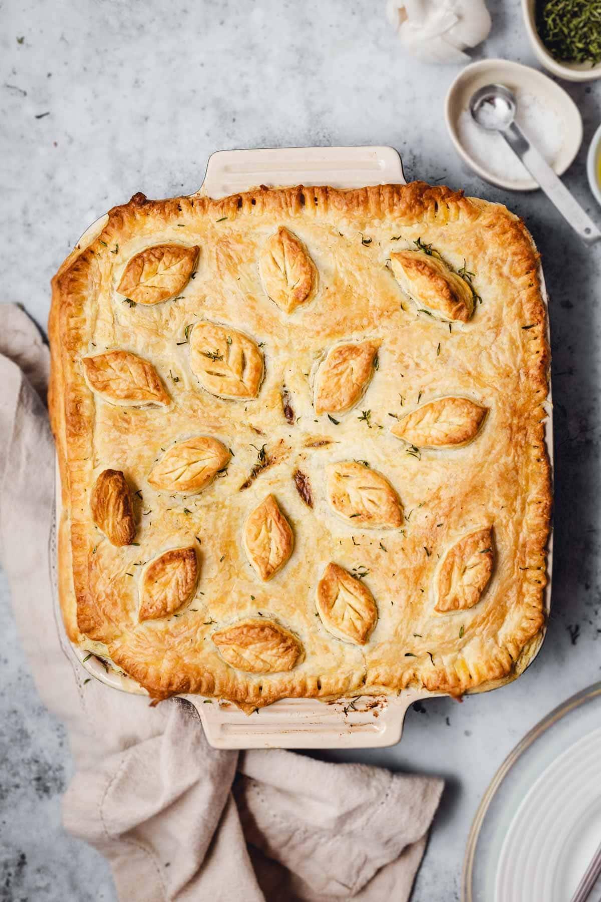 A baked vegan pot pie on a grey background.