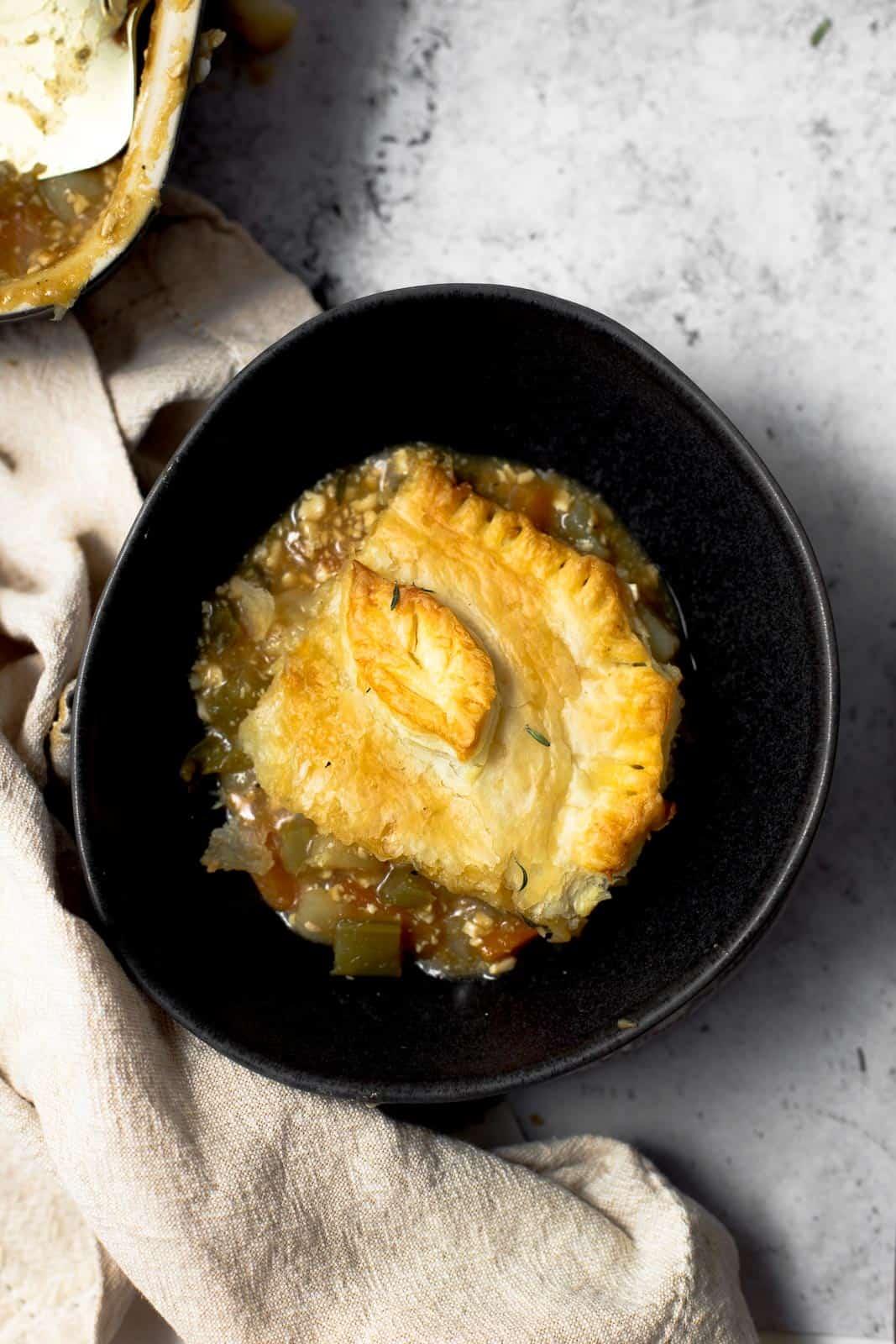 A slice of vegan pie in a large dark bowl.