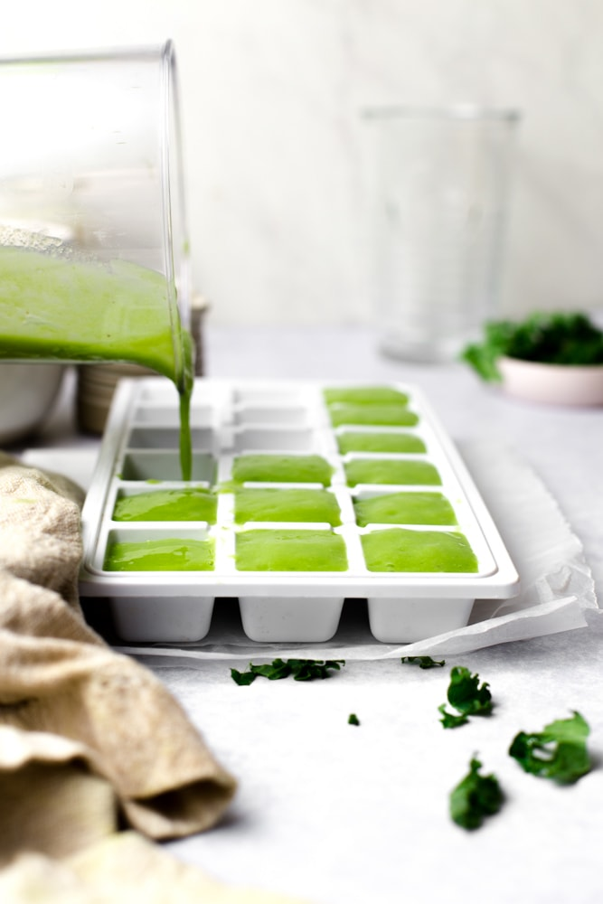 An action shot of green smoothie being poured into an ice cube tray.