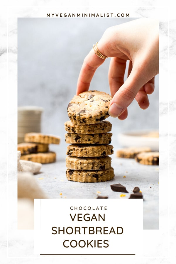 A hand reaching out for a stack of vegan shortbread cookies.