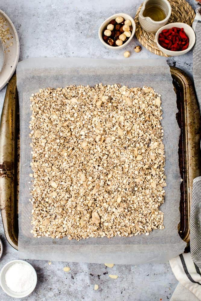 Lined baking tray full of vegan granola before baking.