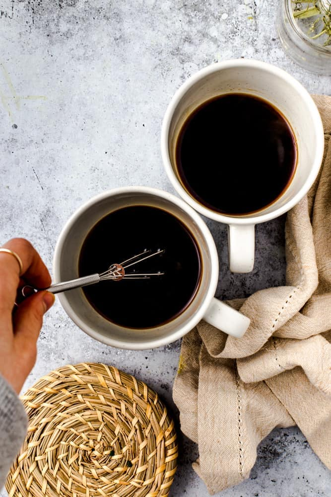 Two coffee mugs and a hand using a whisk to dissolve the coffee.
