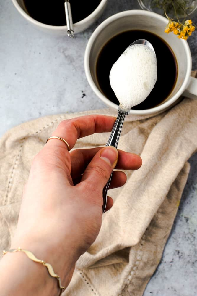 A hand holding out a spoon containing bubbled, foamy oat latte.