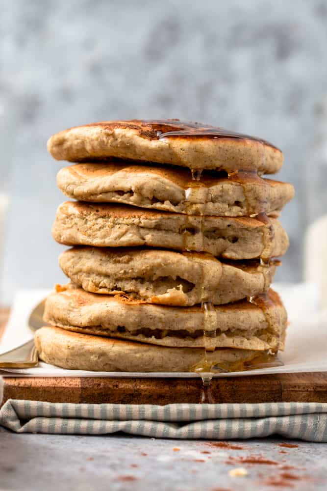 A stack of oat milk pancakes with agave syrup drizzled over.