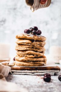 A side view of a stack of oat milk pancakes on a board.
