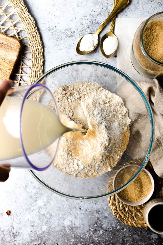 Oat milk being poured on top of dry ingredients to create pancake batter.