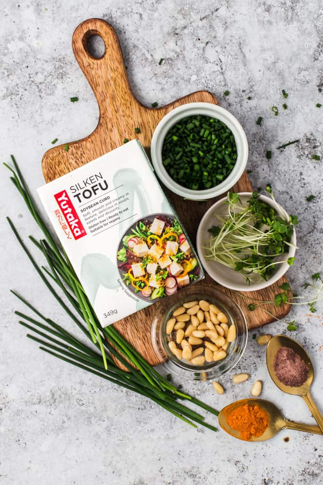 All the ingredients needed to create vegan scrambled egg laid out on a small wooden board.