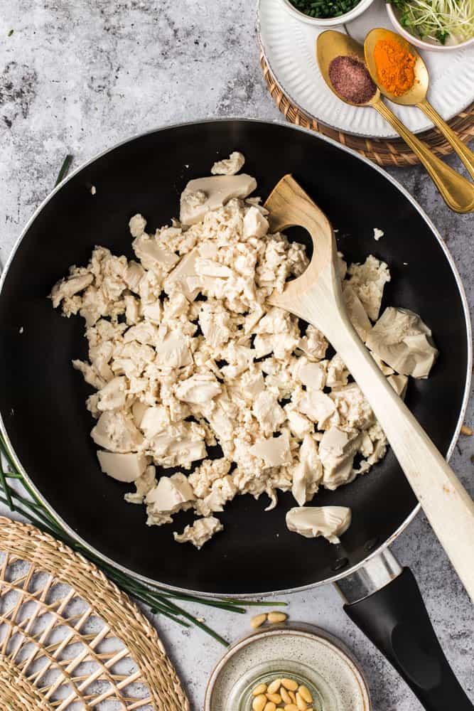 Scrambled tofu added to a large black non-stick pan.