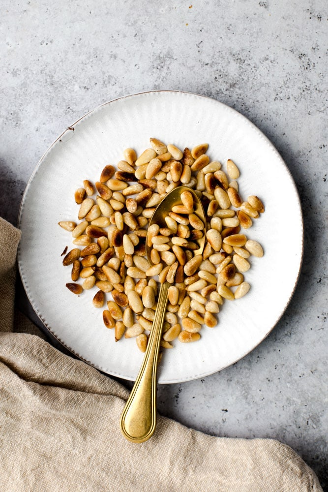 Roasted pine nuts and a spoon on a small white plate.