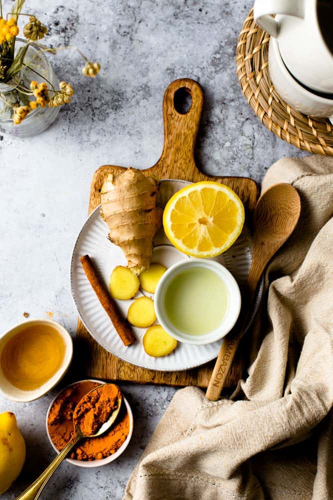 Lemon, ginger, cinnamon and turmeric placed on a small plate on top of a wooden chopping board.