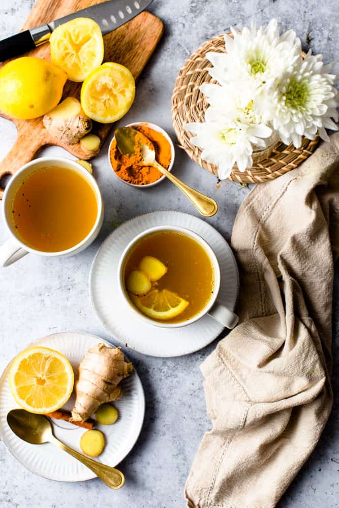 Two cups of cinnamon ginger tea surrounded by pieces of lemon, cinnamon and a small bouquet of flowers.