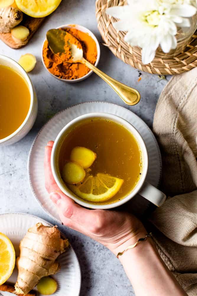 A hand holding a mug of cinnamon ginger turmeric tea placed on a table setting.