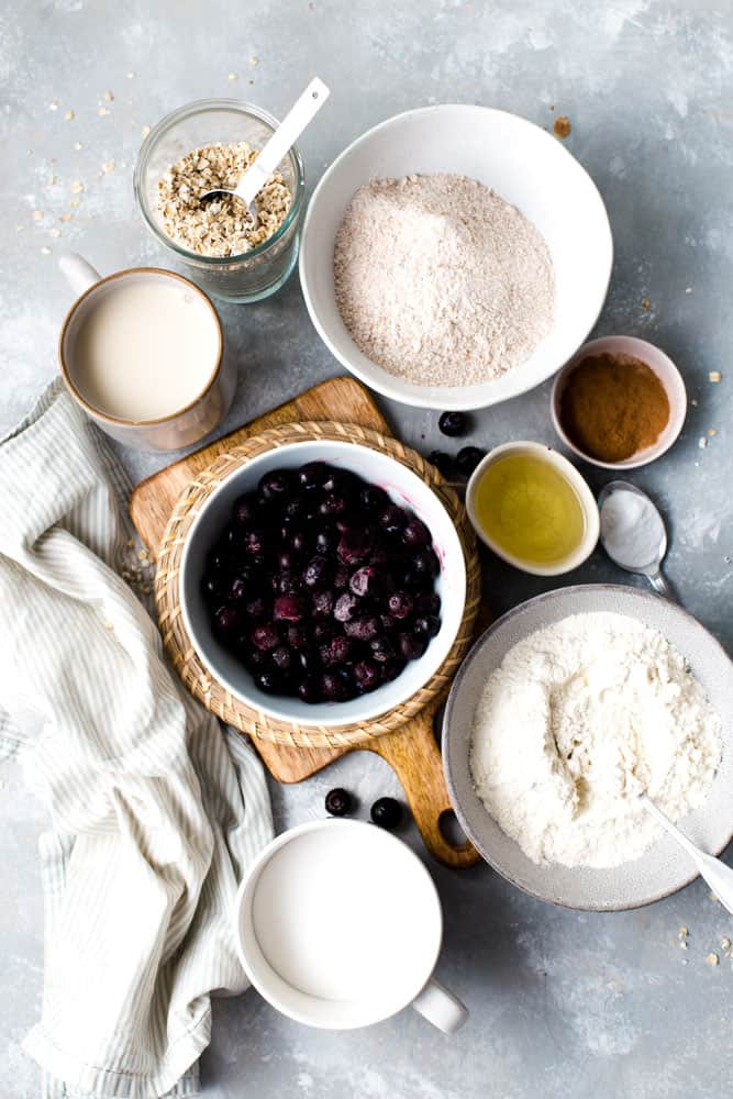 Flour, oats, blueberries, oil and cinnamon laid out in cups and bowls on a flat surface.
