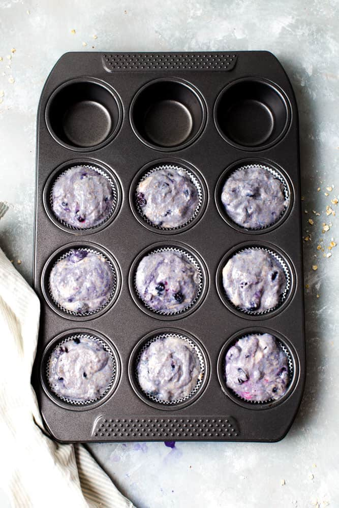 A muffin tray containing raw muffin mixture before baking.