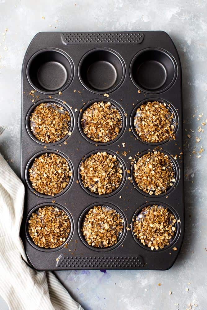 A large muffin tray containing raw muffin mixture placed on a flat surface.
