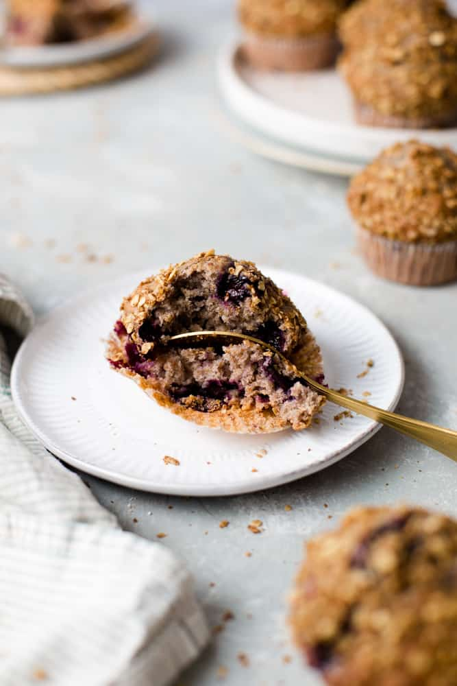 A spoon cutting into a vegan blueberry muffin on a small round plate.
