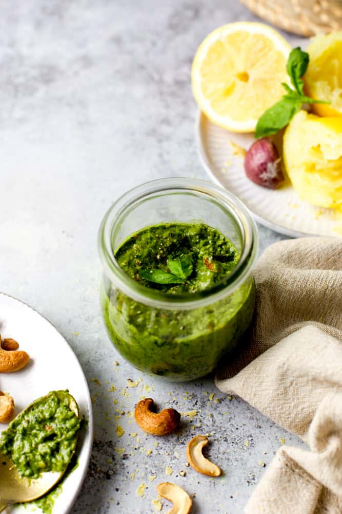 A small glass jar of green pesto with ingredients like lemon, garlic and cashews scattered around it.