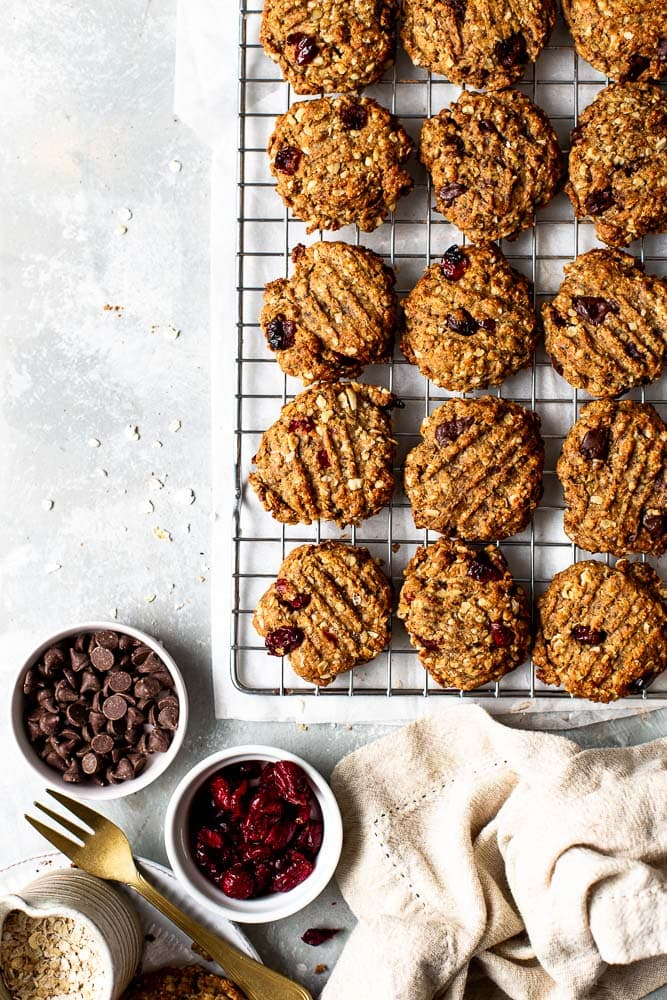 Vegan oatmeal cookies on a cooling rack with chocolate chips and cranberries laid out next to the rack.