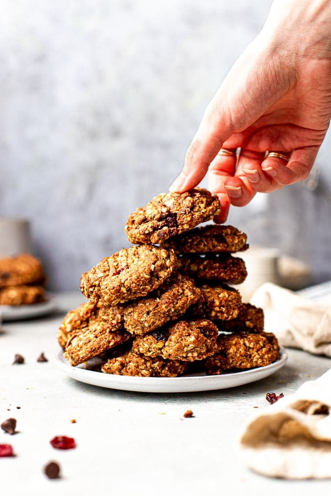 A hand reaching out for a stack of vegan oatmeal cookies.