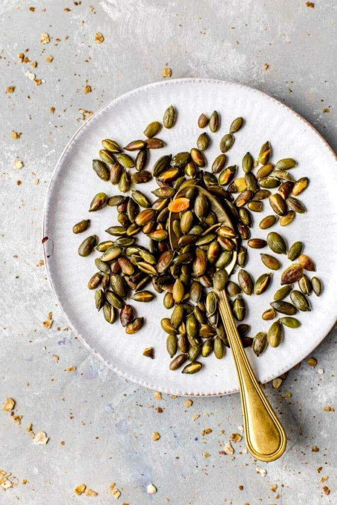 Roasted pumpkin seeds placed on a small round plate.