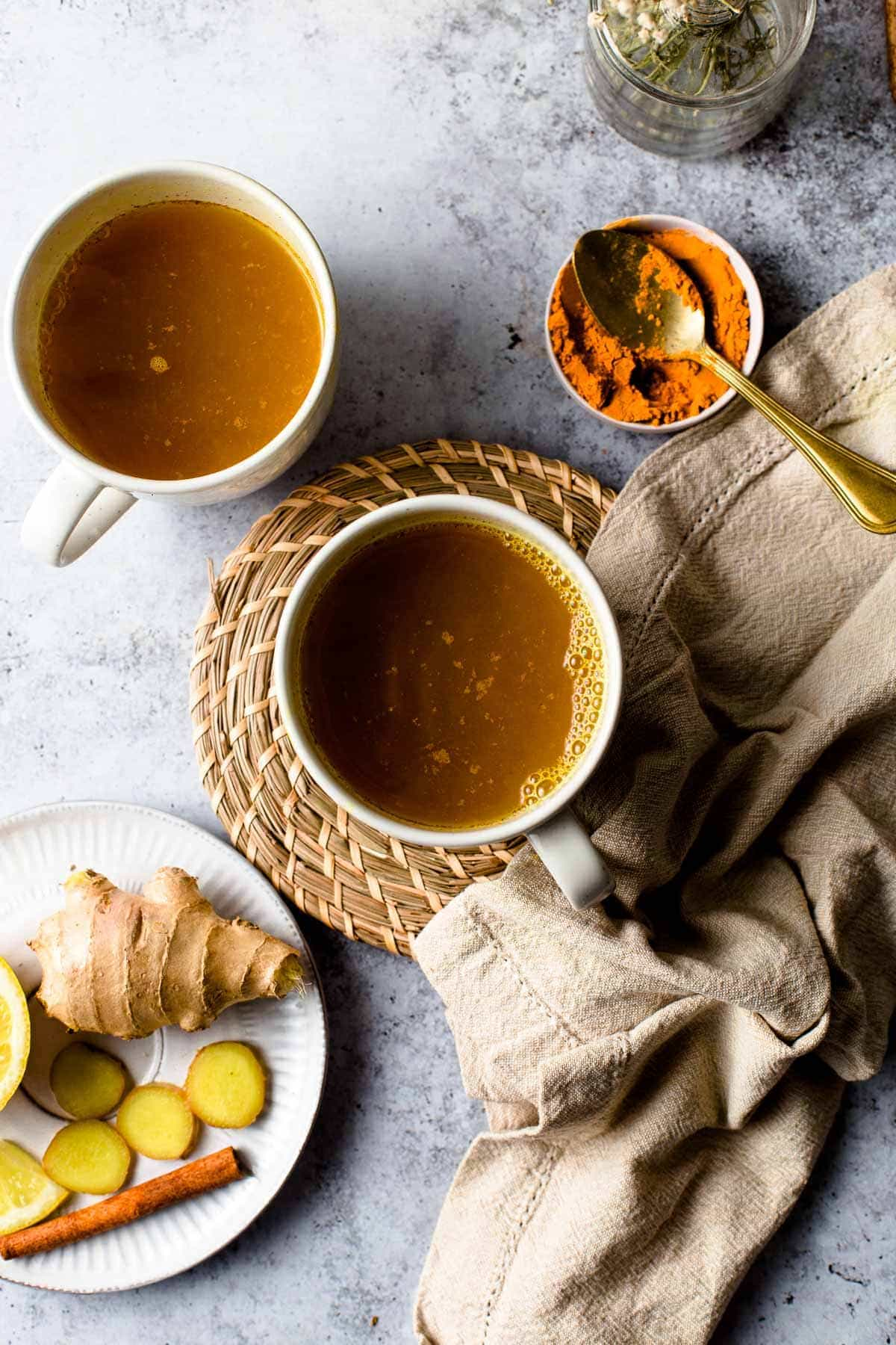 Ginger turmeric lemon tea placed next to a napkin and a small plate.
