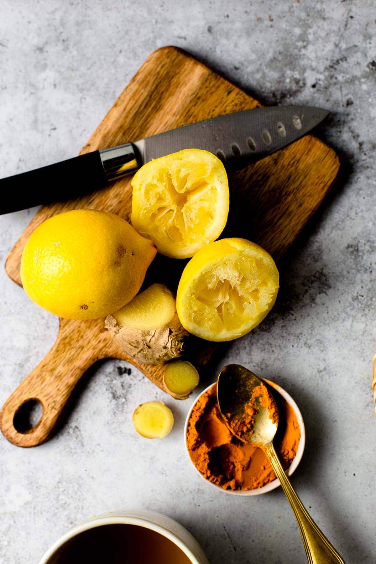 A wooden chopping board featuring lemons, ginger and a small bowl of turmeric.