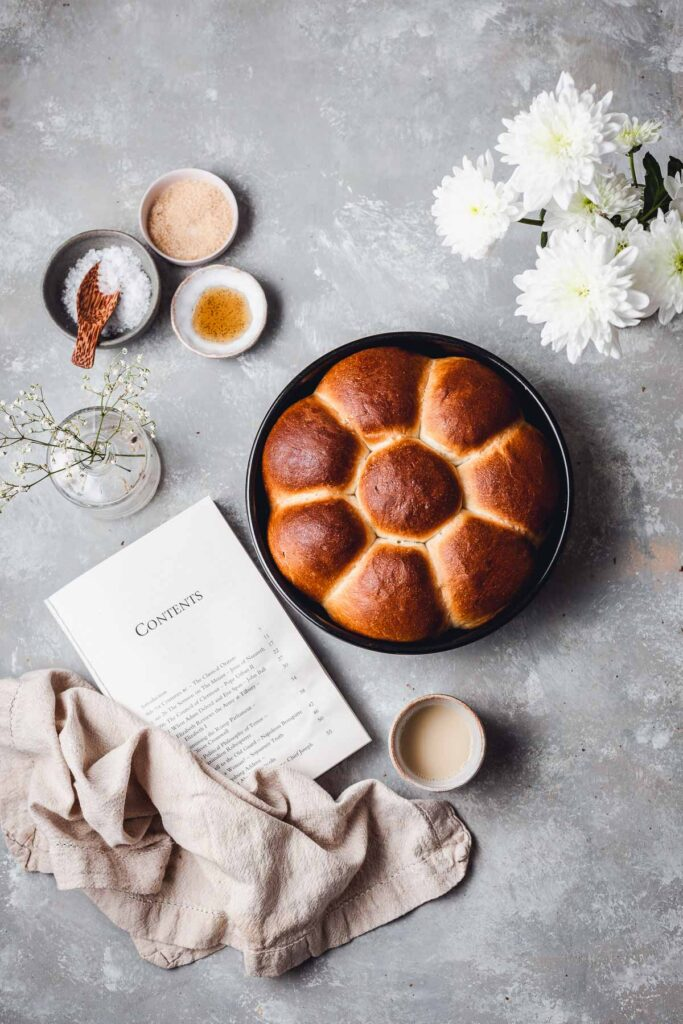 A flatlay scene containing a round loaf of dinner rolls, book, flowers, napking and ingredients.
