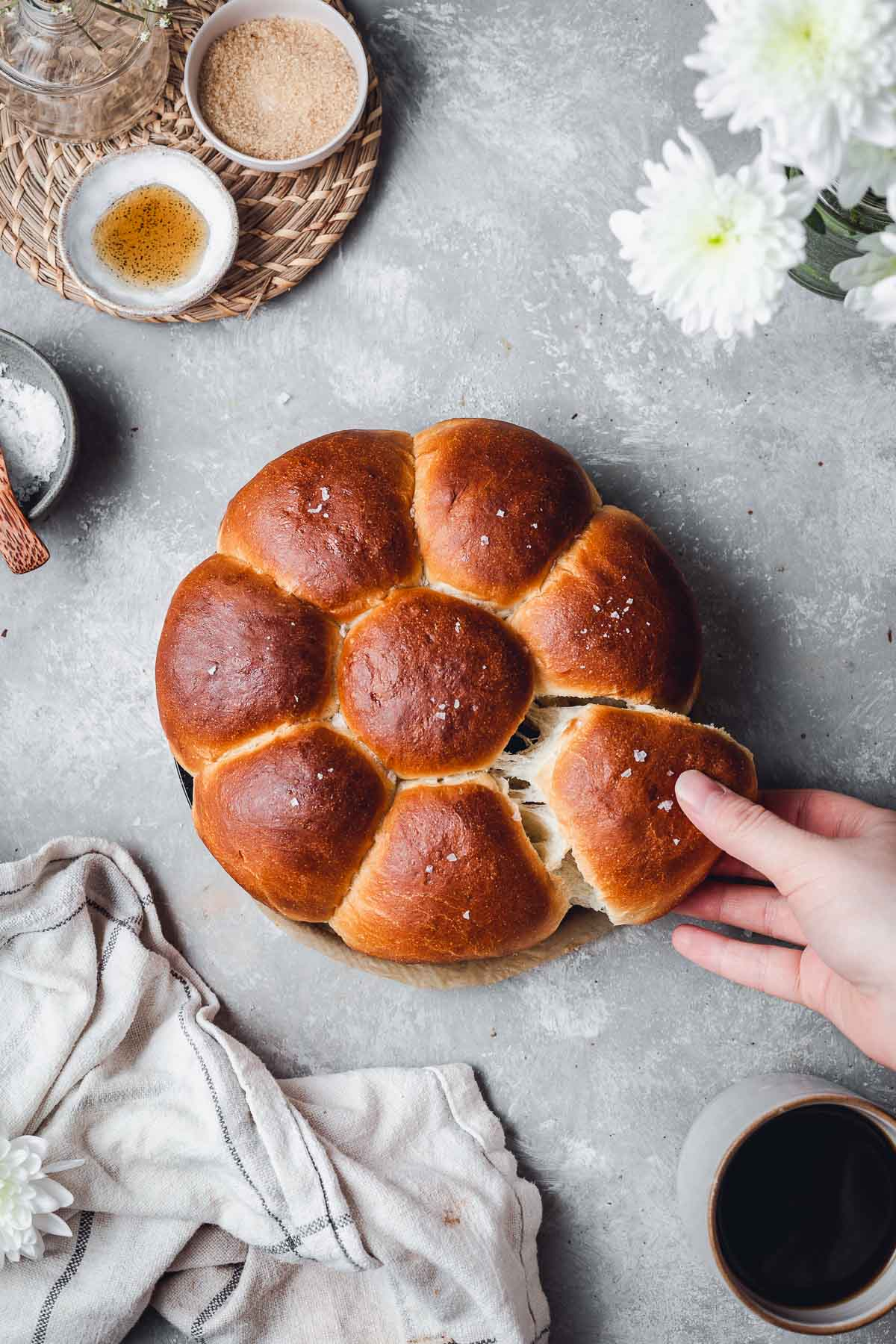 An overhead view of dinner rolls with one hand pulling apart one roll.