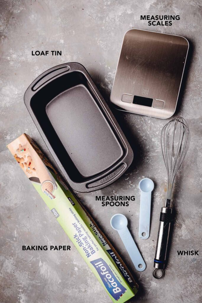 Various baking equipment like measuring spoons, scales and a tin on a flat surface.