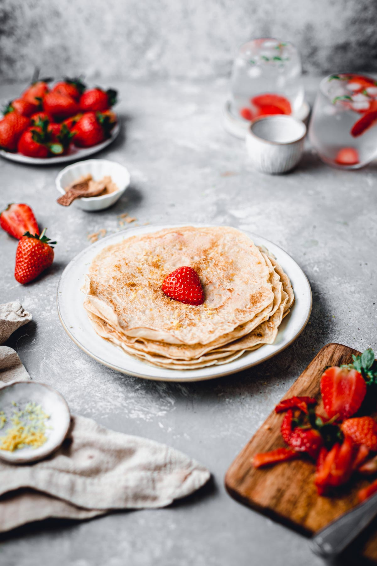 A side view of a almond milk crepes stacked on a round plate with a single strawberryb on top.