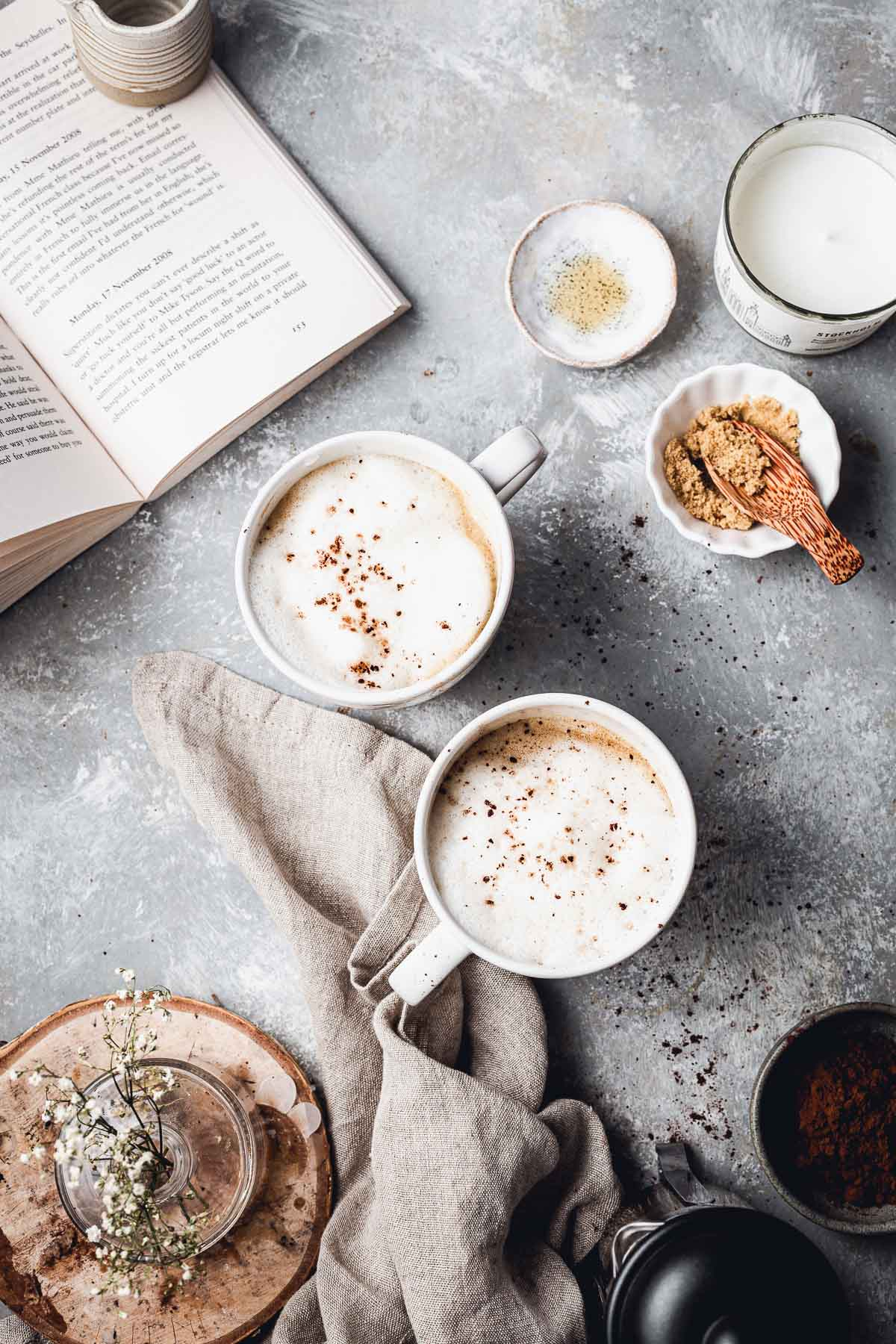 An overhead view of a table with two latte mugs, book and various props laid around it.
