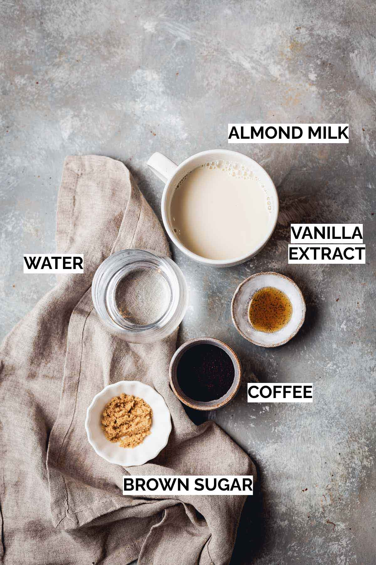 All five ingredients needed to make a latte laid on a flat grey surface.