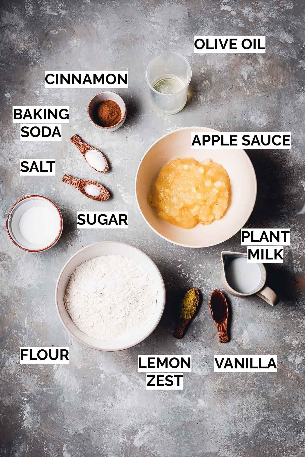 All ingredients needed to bake vegan apple sauce cake laid on a flat background.