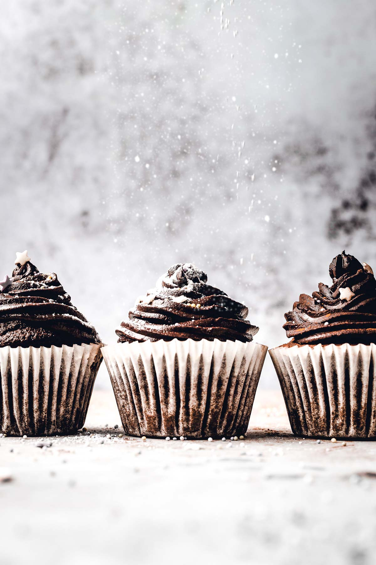 Three chocolate cupcakes side by side being dusted with powdered sugar.