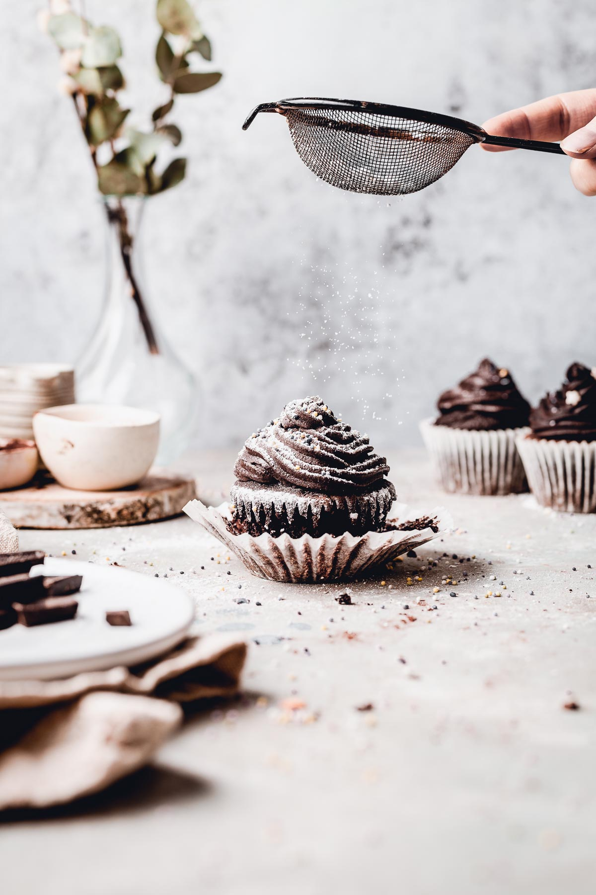 A hand dusting a single chocolate cupcake with powdered sugar.