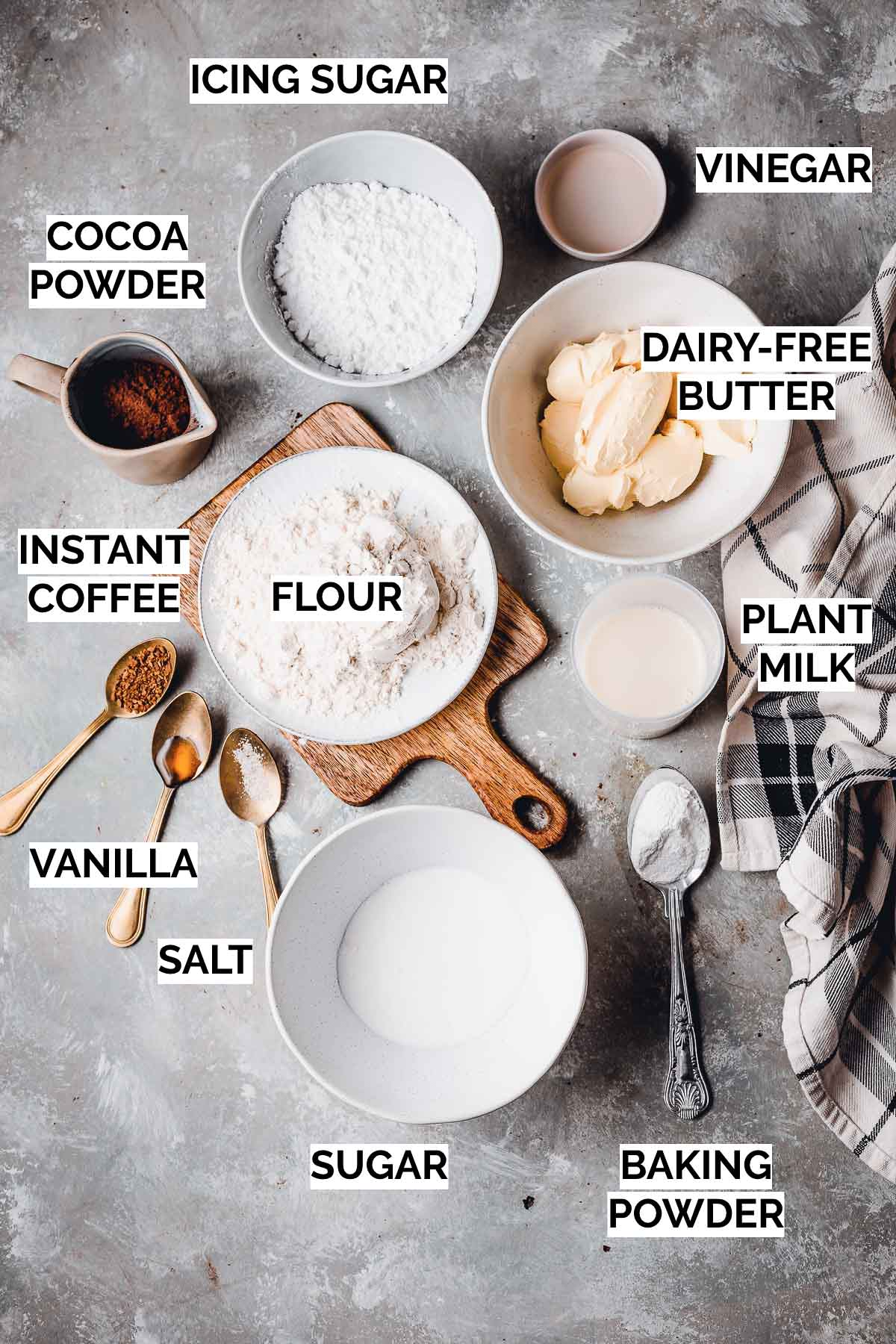 Ingredients needed to make vegan cupcakes on a flat surface.