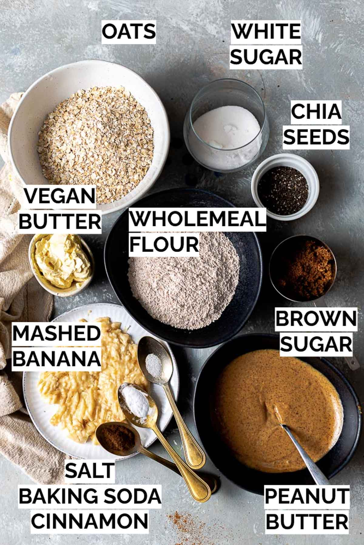 All ingredients needed to make oatmeal cookies laid out in bowls.