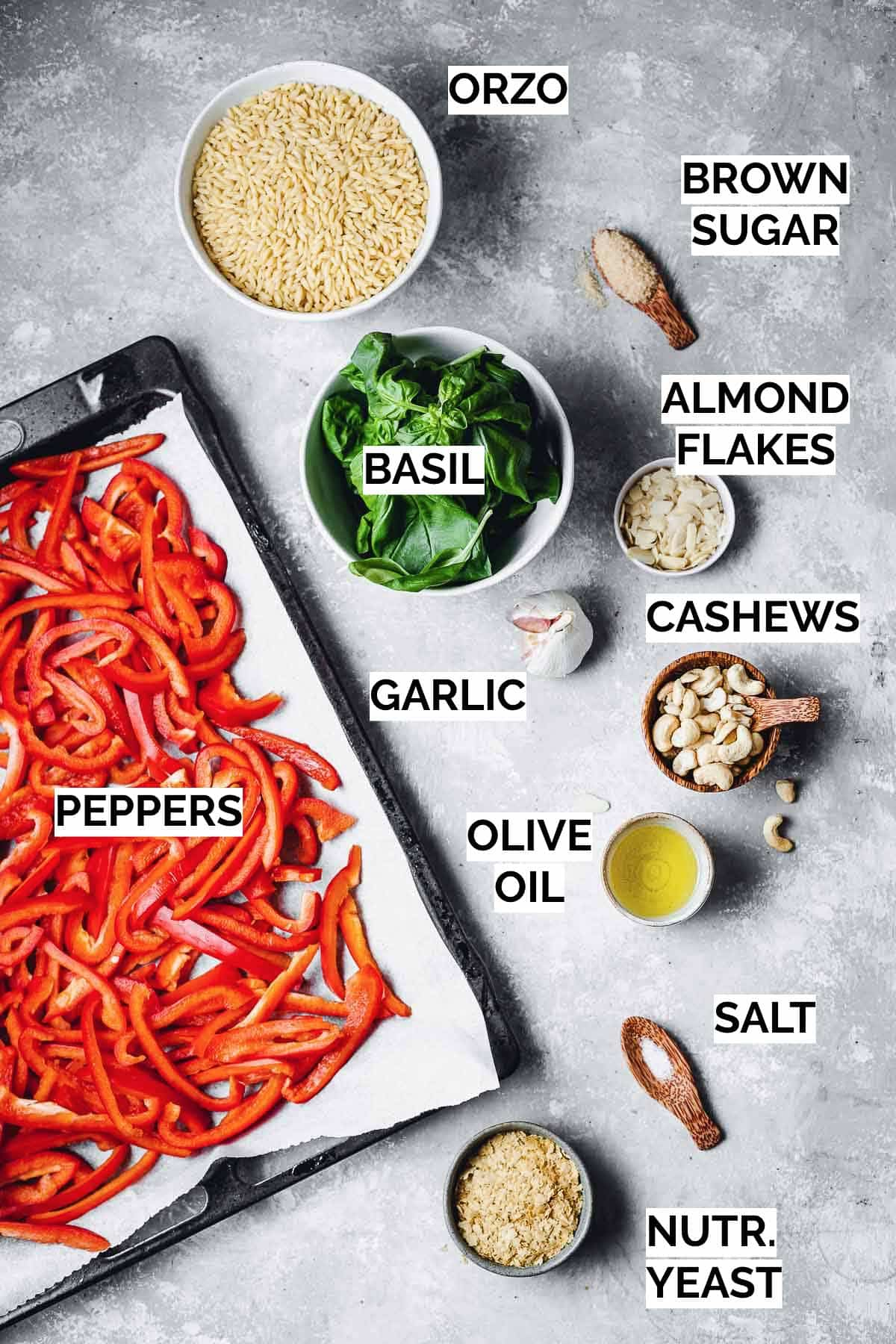 All the ingredients needed to make vegan orzo pasta laid out on a flat surface.