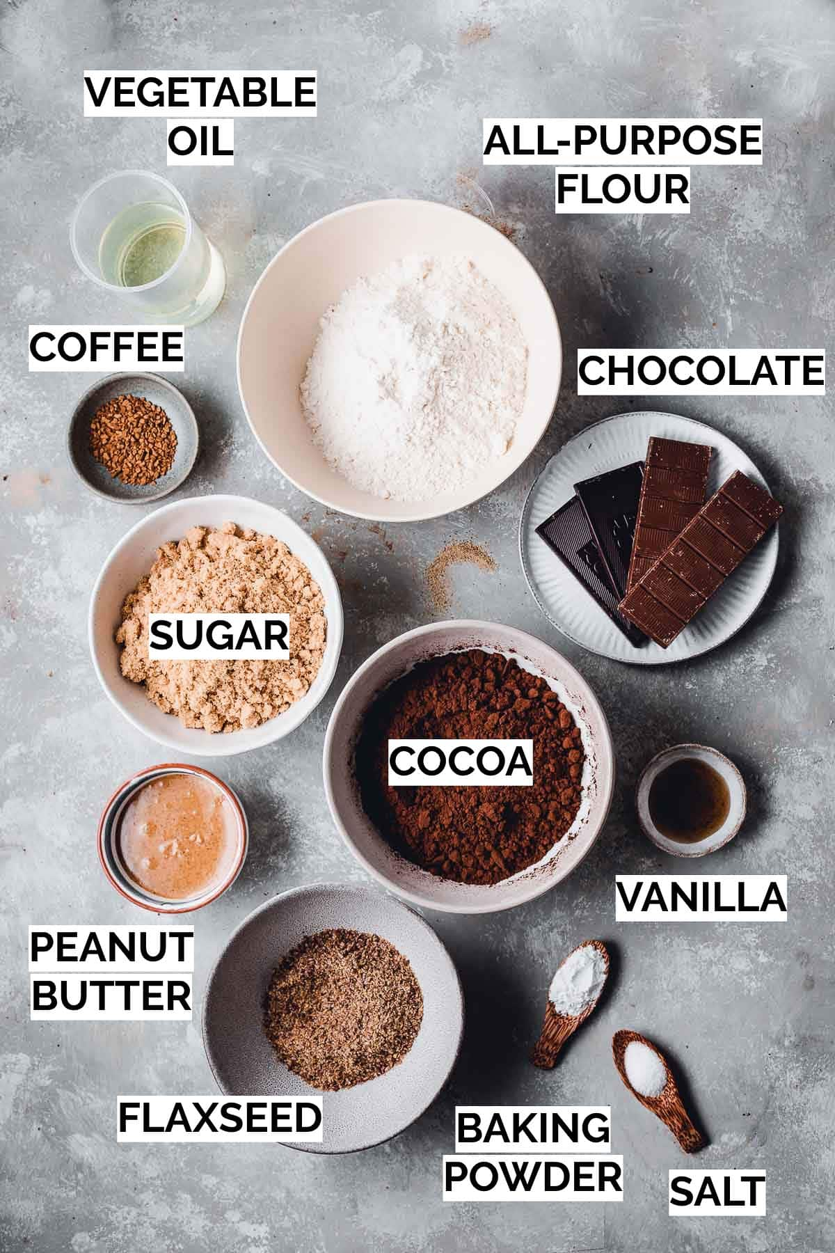 Various ingredients needed to make chocolate brownie shown on a flat surface.