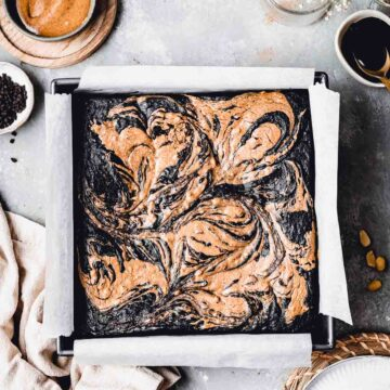 An overhead shot of baked brownie in a baking tin surrounded by various ingredients.