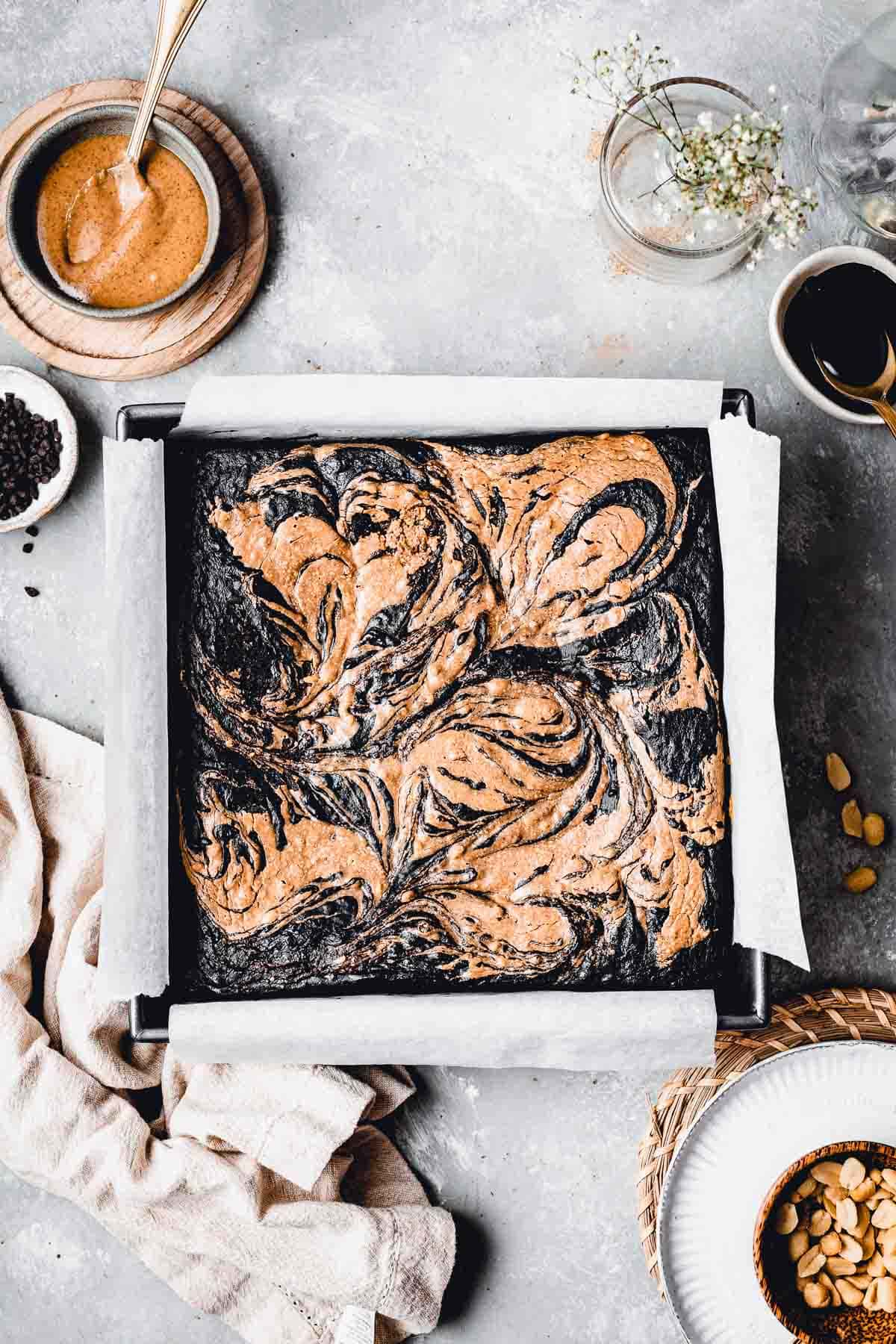 Swirled vegan peanut butter brownie in a square shaped baking tin shown from the top.