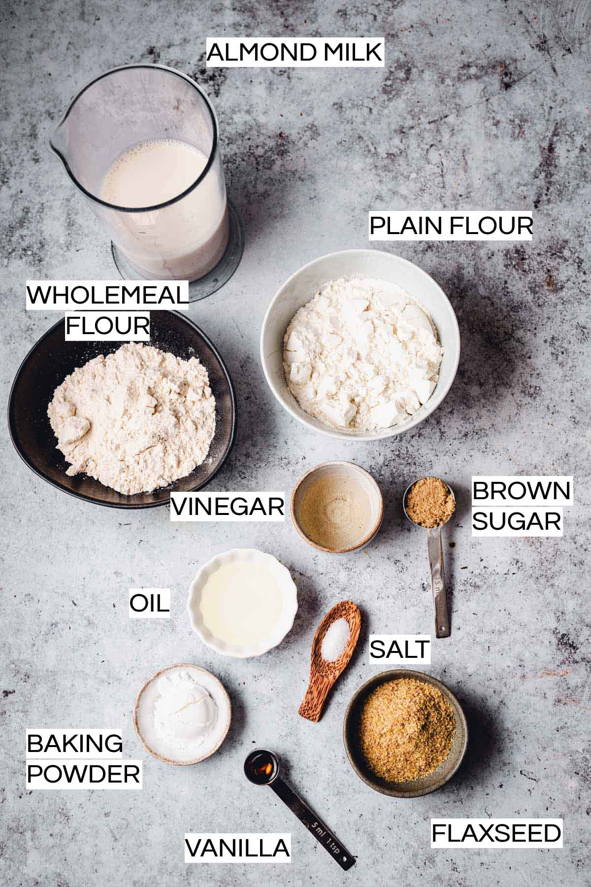All ingredients needed to make waffles laid out on plates and bowls.