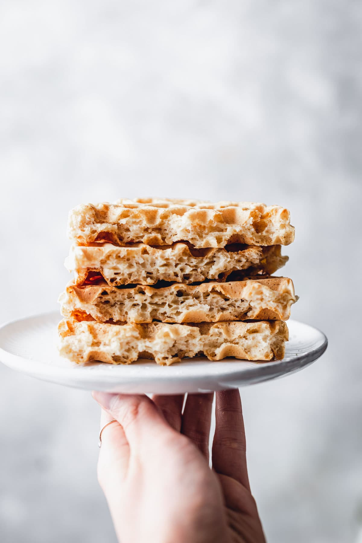 A stack of almond milk waffles on a small plate being held up by a hand.