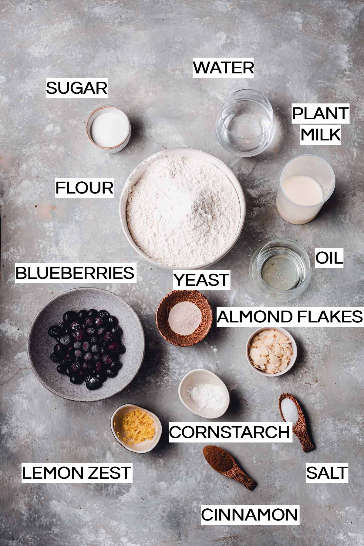 All the ingredients needed to make blueberry buns placed in cups and bowls.