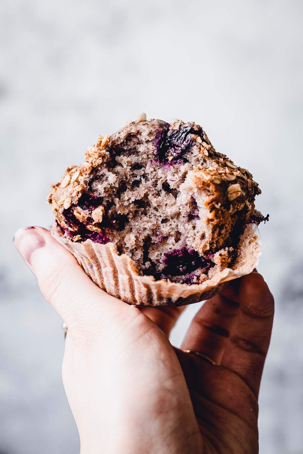 A hand holding up one blueberry muffin with a bite taken out of it.